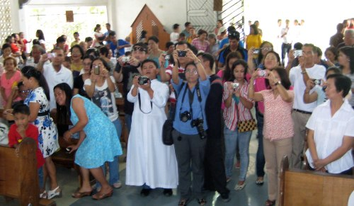Family and friends quickly try to get photos of their loved ones after the ordination