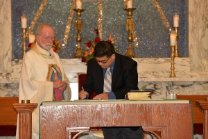 Joseph signs his vow renewal while Fr. Ed Kilianski, pastor of OLG, looks on.