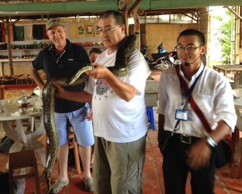 Fr. Wayne shows off his adventurous side in Vietnam, holding a python during travels with Fr. Steve.