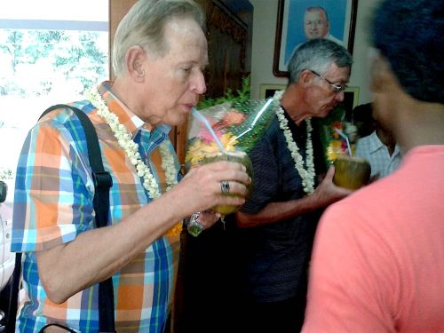 Fr. Jim and Fr. Tom as welcomed with flowers and coconut milk